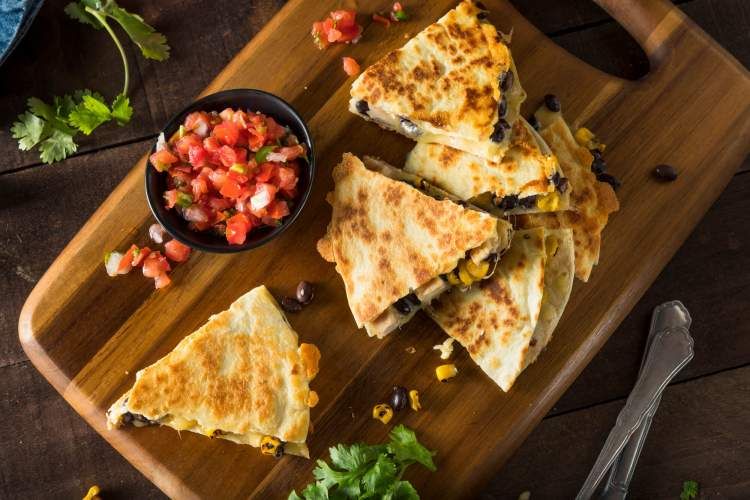 Healthy chicken quesadillas cut into wedges with salsa, limes, and cilantro on the side.