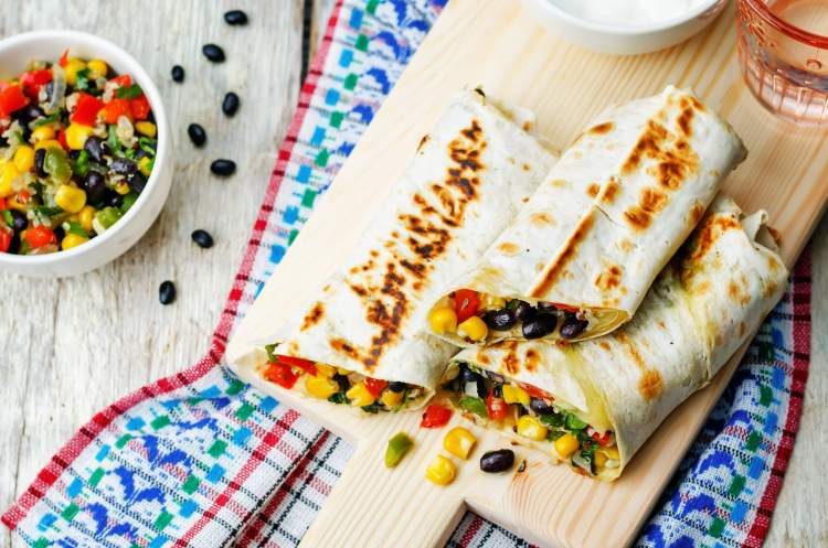 Freezer Friendly Burritos on a wooden table with herbs and napkins.