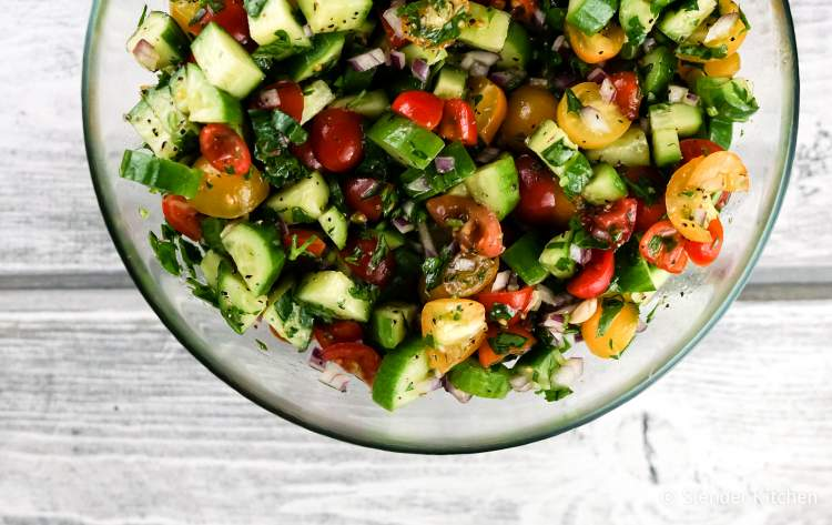 A low carb side dish salad with cucumbers, tomatoes, red onion, and a lemon and olive oil dressing.