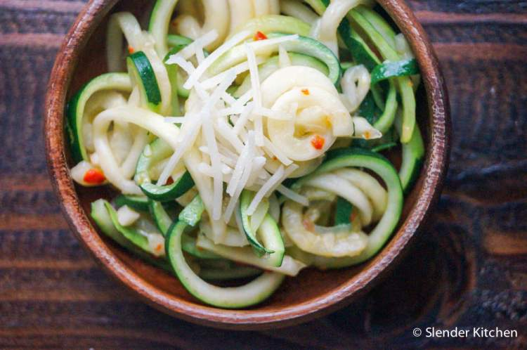 Zucchini noodles in a wooden bowl with Parmesan cheese and red pepper flakes.