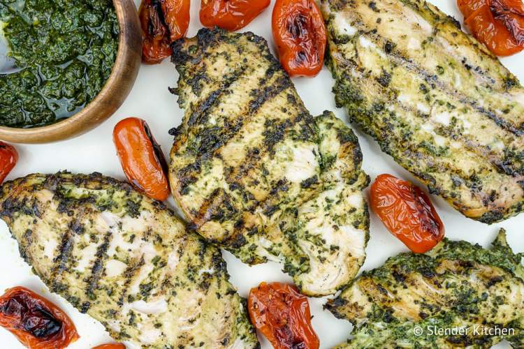 Pesto Chicken with cherry tomatoes on a white table.
