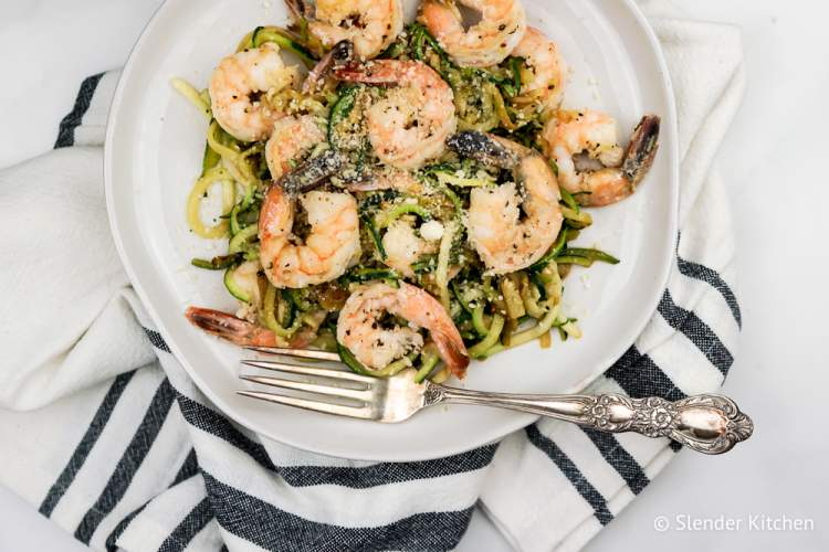 Pesto shrimp with zucchini noodles on a white plate with a white napkin.