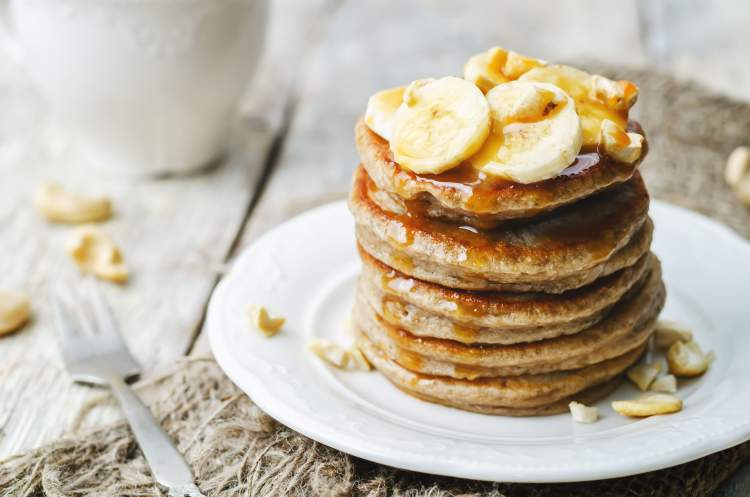 Protein Packed Banana Pancakes in a stack with maple syrup and banana slices..