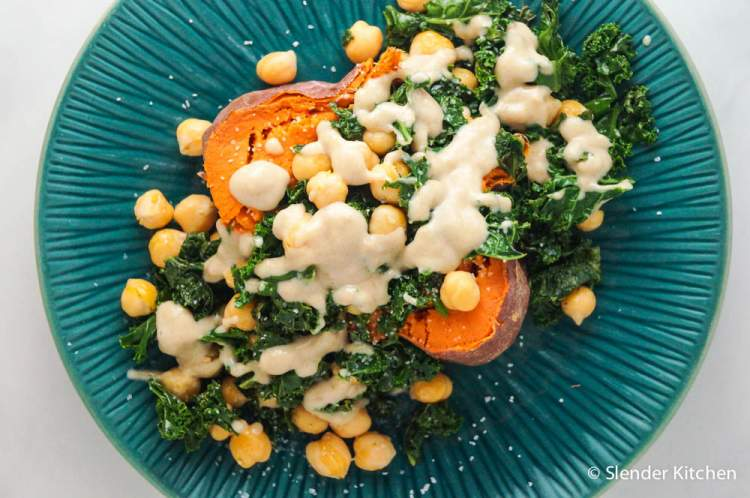 Baked sweet potato with chickpeas and kale on a blue plate.