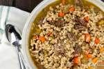 Healthy Beef and Barley Stew made in the Instant Pot in a ceramic bowl with a napkin.