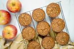 Applesauce oatmeal muffins with oatmeal flecks on a baking rack with a yellow napkin and apples.