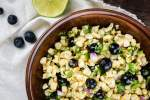 Blueberry corn salad with red onions and herbs in a bowl.