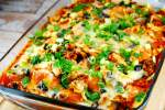 Chicken enchilada casserole with green onions and olives in a baking dish.