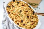 Healthy cornbread sausage stuffing with dried cranberries and thyme in a baking dish.
