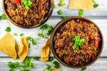 Healthy Turkey chili in two bowls with cilantro and tortilla chips.