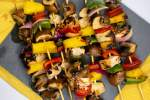 Hawaiian Chicken Kabobs with pineapple, mushrooms, and bell peppers on wooden skewers.