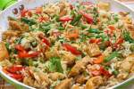 Healthy chicken fried rice with veggies on a large plate.