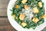 Kale caesar salad with croutons and Parmesan cheese on a plate with a fork.