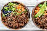 Korean beef with vegetables and rice in a wooden bowl.
