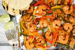 Shrimp fajitas on a baking sheet with sliced peppers, onions, tortillas, and limes.