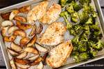 Roasted chicken with potatoes and broccoli on a sheet pan.