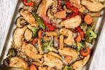 Sheet pan Asian chicken stir fry with chicken breast, peppers, broccoli, and other veggies on a sheet pan.