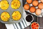 Black bean egg muffins in a muffin tin with eggs, black beans, and red pepper on the side.