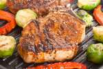 Grilled pork chops with southwestern seasoning on a grill with brussels sprouts and peppers.