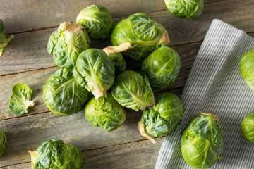 Brussel sprouts on a cutting board with a white napkin.