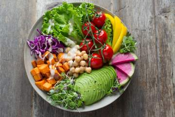 Clean eating dish with avocado, tomatoes, peppers, cabbage, carrots, and chickpeas.