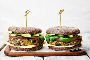 Veggie burgers with vegetables on a gluten free roll.