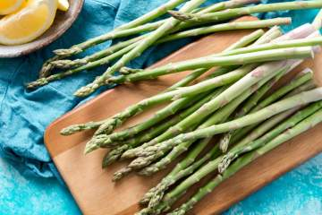 Asparagus spears on a cutting board with lemon slices.