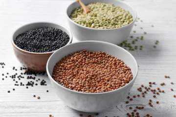 Three types of lentils including brown, black, and green in bowls.