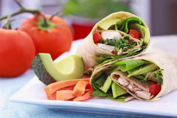 Vegetable wrap sandwiches with avocado, carrots, and lettuce.