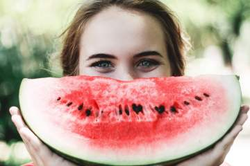 Woman holding a watermelon slice  in front of her face.