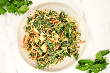 This easy Asian Kale Apple Slaw packed with fresh kale, cabbage, carrots, mint, and cilantro in a creamy peanut vinaigrette makes a delicious side dish or add chicken or tofu for a healthy meal.