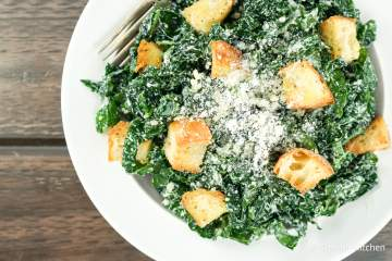 Healthy Kale Caesar Salad with a homemade yogurt Caesar dressing that you will never believe is lightened up. Paired with kale and some quick homemade croutons, it's one of the best kale salads around.