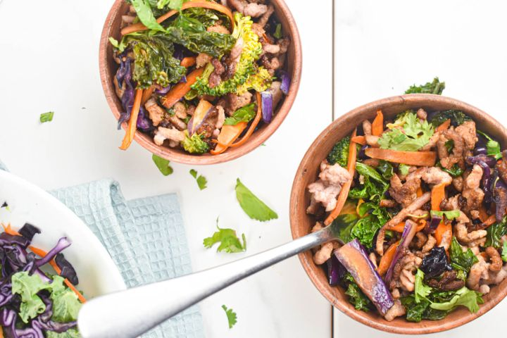 Asian ground turkey stir fry with kale, carrots, broccoli, and soy sauce in two bowls.