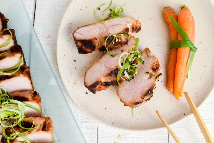 Asian grilled pork tenderloin on a plate with carrots, green onions, and chopsticks.