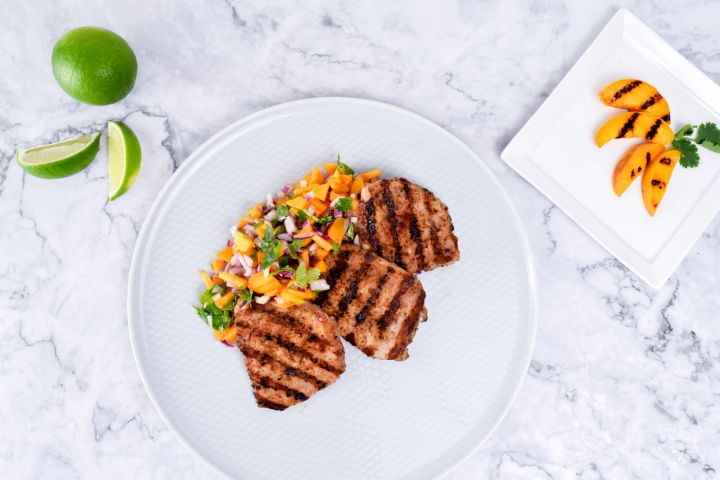 Grilled pork chops with peach salsa with fresh limes and peaches on the side.