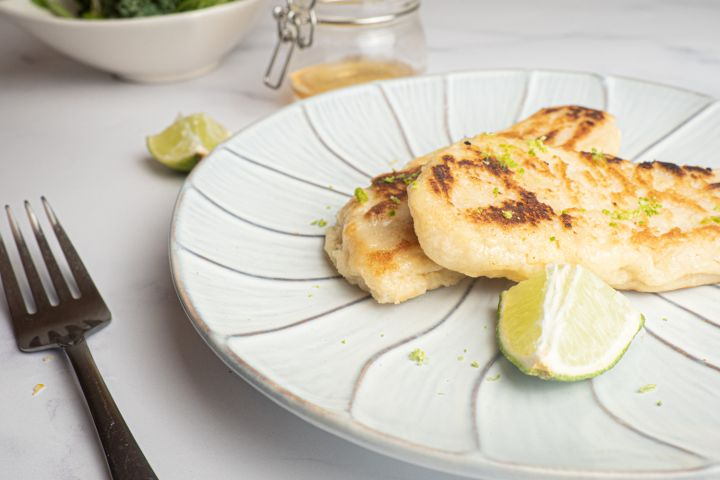 Tilapia with honey and lime cooked until crispy on a plate with a lime and fork.