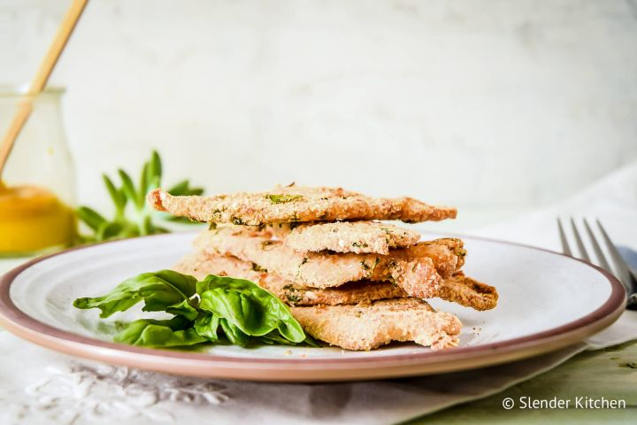 Parmesan crusted chicken piled on a plate with fresh basil and a fork.