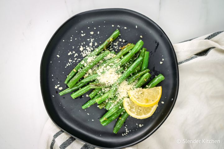 Parmesan green beans with lemon and garlic on a black plate.