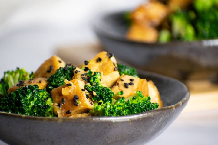 Sesame tofu with broccoli and sesame seeds in a small gray bowl.
