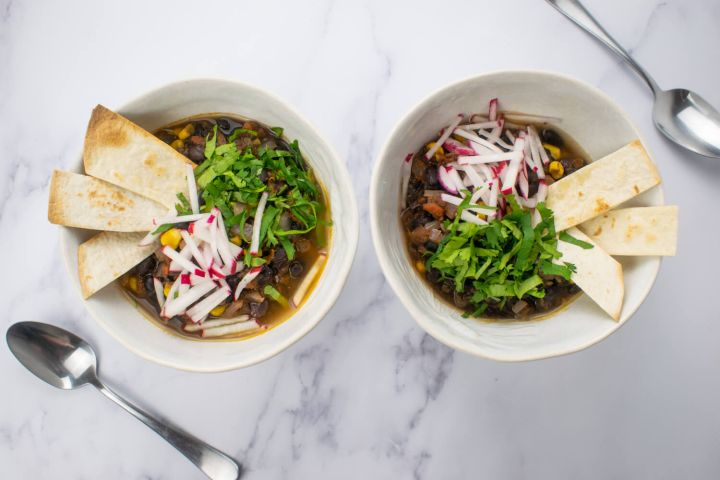 Vegetarian tortilla soup with radishes and cilantro on top with crispy tortilla strips.