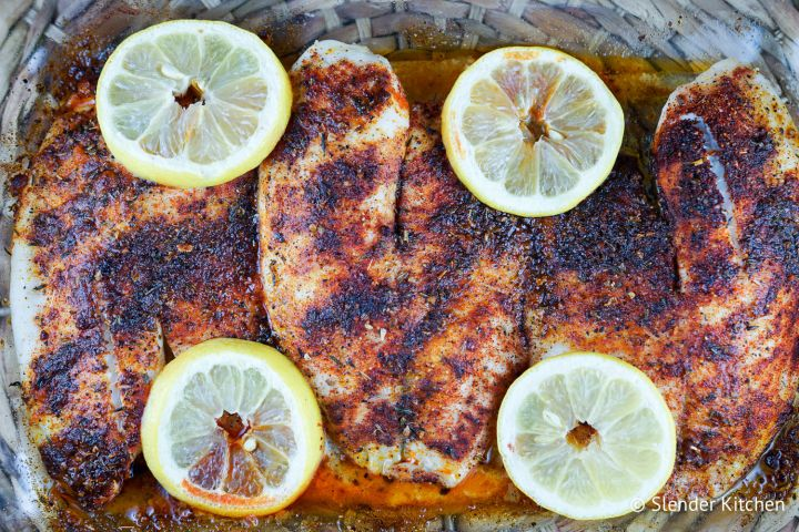 Blackened tilapia in a glass baking dish with lemon slices and blackening seasoning.
