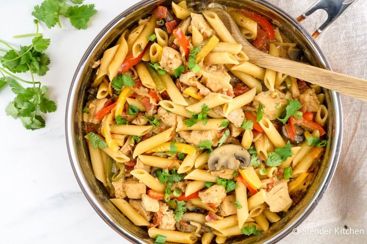 Chicken Fajita Pasta in a skillet with mushrooms, peppers, onions, and tomatoes.