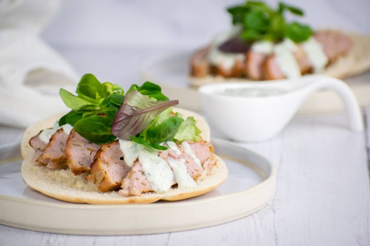 Chicken gyros with tzatziki on pita bread with lettuce.