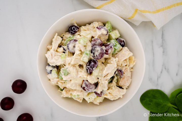 Chicken salad with grapes, celery, and yogurt dressing in a bowl with grapes and spinach on the side.
