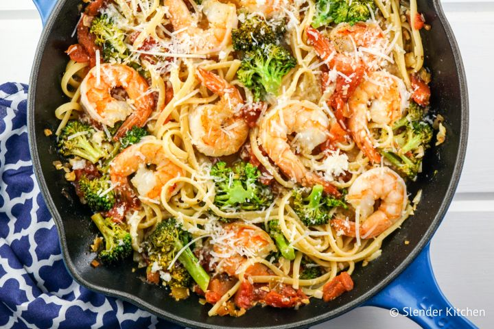 Garlic lemon and shrimp and broccoli pasta in a pan with fresh lemon slices and Parmesan cheese.