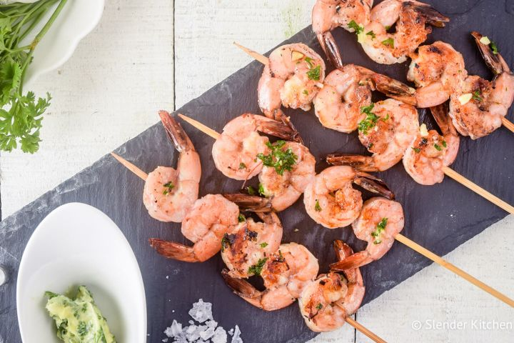Garlic lemon shrimp kabobs on a piece of slate with garlic and parsley.