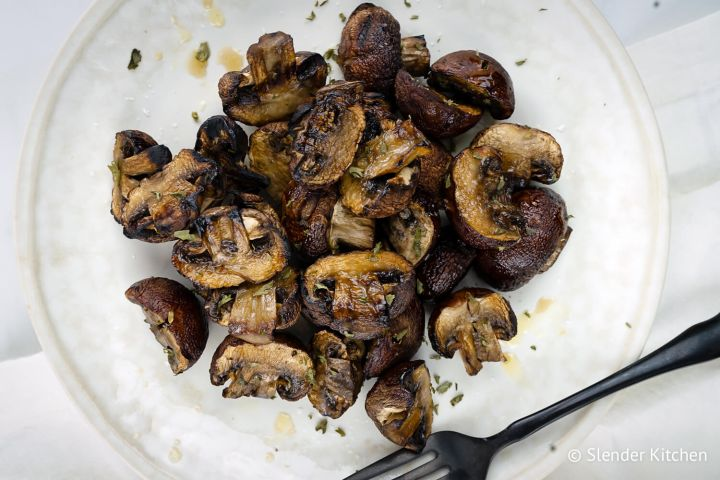 Grilled mushrooms with balsamic vinegar, olive oil, and garlic on a plate.