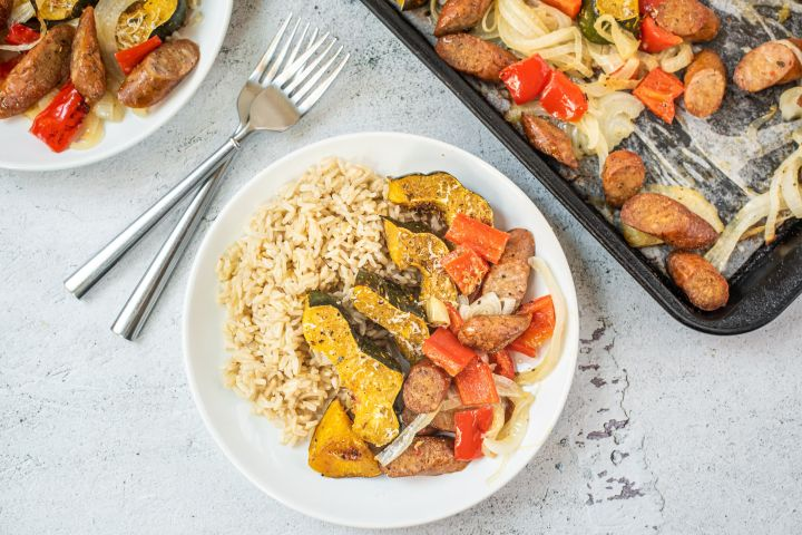 One pan sausage and acorn squash with bell peppers and onions on a plate with brown rice.