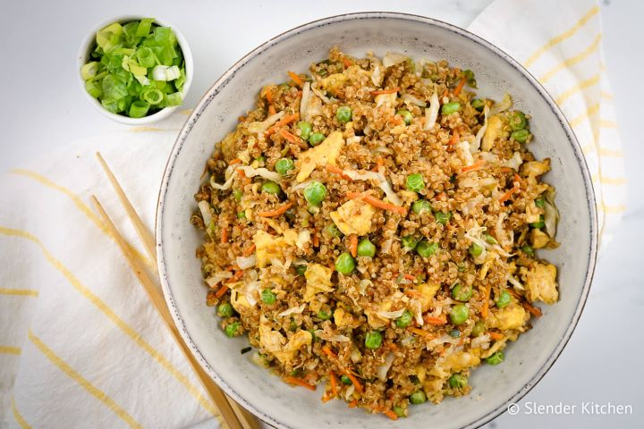 Quinao fried rice with peas, cabbage, eggs, and soy sauce in a bowl with chopsticks.