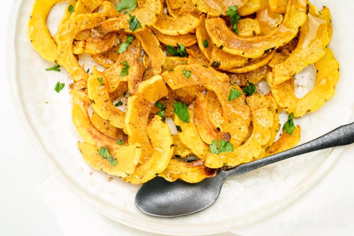 Roasted delicata squash with brown sugar and cinnmon on a white plate.